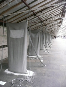 """The curator's favourite installation. Handmade """"sacks"""" stretching from floor to ceiling. Underneath is a pool of dust, as though they haven't been used for years. I thought this piece by Hilary Bower captured the disused mill environment, and was a perfect and moving fit for the empty Spinning Room"""