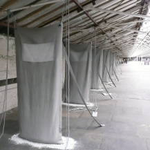 "The curator's favourite installation. Handmade ""sacks"" stretching from floor to ceiling. Underneath is a pool of dust, as though they haven't been used for years. I thought this piece by Hilary Bower captured the disused mill environment, and was a perfect and moving fit for the empty Spinning Room"